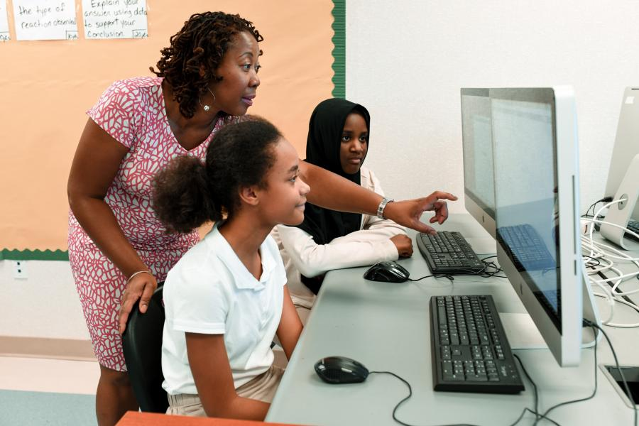 Instructor teaching two girls how to write computer code